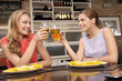 Pretty women clinking goblets of beer