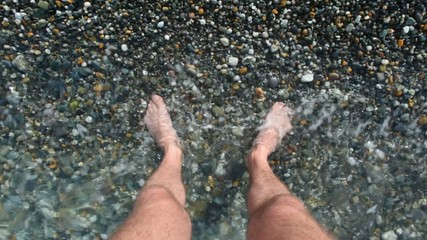 male foots of adult man standing in sea surf, first person video
