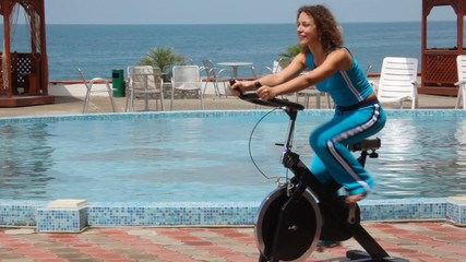 young woman training on exercise bicycle, pool and sea