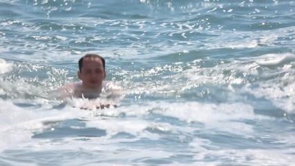 caucasian man swimming in waving sea