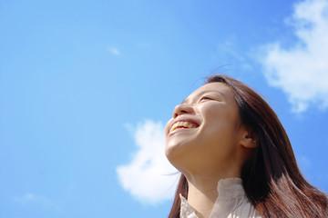 笑顔で空を見上げる女性