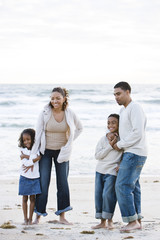 Happy African-American family standing together on beach
