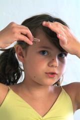 Eine junge Mädchen mit einer Haarspange in der Hand.
