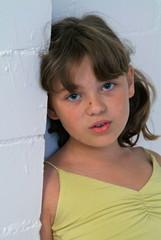 Eine junge Mädchen mit ernstem Gesicht posiert an der Wand.