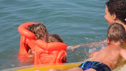woman with girls and boy on inflatable mattress has fun in sea