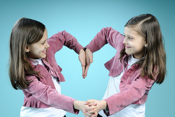 twins having fun and creating heart from hands