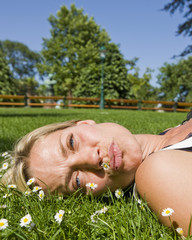 Headshot of a woman lying in the grass and relaxing