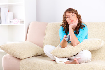 Unhappy woman sitting on sofa with remote controller