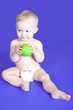 Baby boy is eating green apple