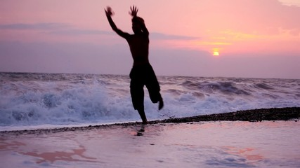 silhouette of happy running and jumping man on beach