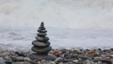 stone stack on pebble coast, waving sea in background