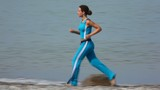 woman in tracksuit running on coast, sea in background