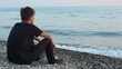 teenager sits on pebble beach and looks at sea, back view