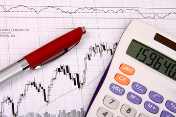 White calculator and a red pen on a financial chart