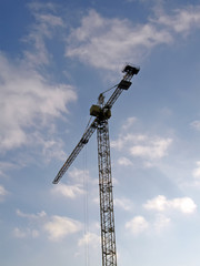 high crane silhouette on blue sky, clouds