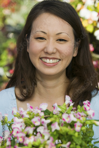 woman holding flowers in plant nursery portrait close up