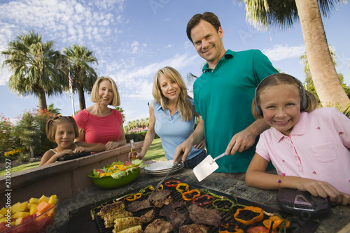 girl (7-9) listening to portable music player at outdoor barbecue with sister (7-9) parents and grandmother portrait.