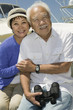 senior couple with binoculars on boat (portrait)