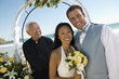 bride and groom with priest under archway at ocean (portrait)