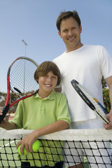 father and son at tennis net portrait