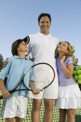father with son and daughter by net on tennis court portrait front view