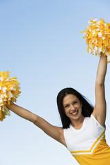 smiling cheerleader rising pom-poms (portrait)