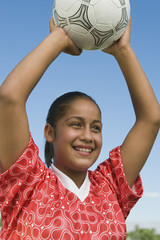 girl (13-17) throwing in soccer ball portrait
