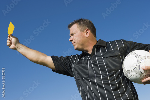 soccer referee holding yellow card portrait