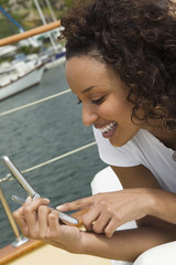 woman lying on yacht using mobile phone (close-up)