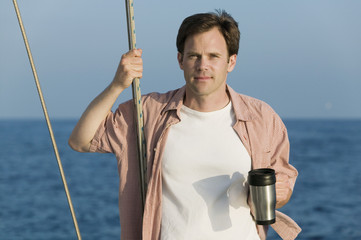 man standing on sailboat holding coffee mug (portrait)