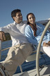 young couple sitting at steering wheel on sailboat