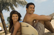 surfer couple sitting back to back against surfboard on beach