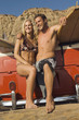 young couple in swimwear leaning on back of truck with surfboards