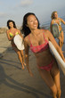 three female surfers carrying surfboards walking on beach