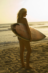 female surfer carrying surfboard on beach at sunset back view