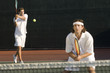 tennis player hitting backhand; doubles partner squatting at net