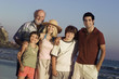 three generation family standing together on beach at dusk portrait