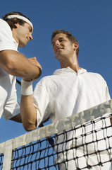 tennis players shaking hands at net low angle view
