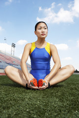 female athlete stretching on field