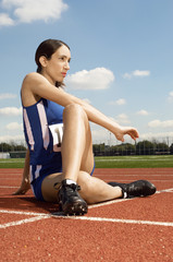 female athlete stretching on running track
