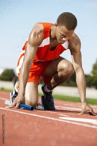 runner waiting in starting block holding baton