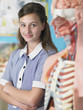 high school student standing by anatomical model in classroom  portrait
