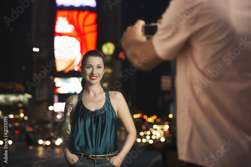 man  photographing elegant woman in times square at night