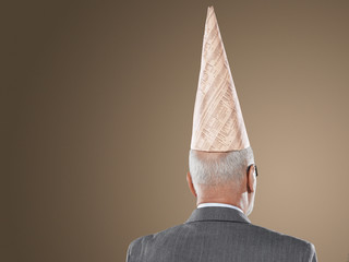 businessman wearing dunce hat back view head and shoulders