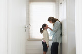 mother cupping daughters face in hands standing by window