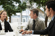 three businesspeople in meeting outdoors