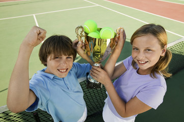 brother and sister on tennis court holding up trophy portrait high angle view