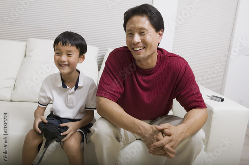 father watching son play video game on couch front view