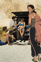 rock climber holding rope with friends sitting by truck  (portrait)