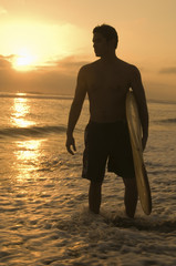 surfer standing in surf holding surfboard at sunset